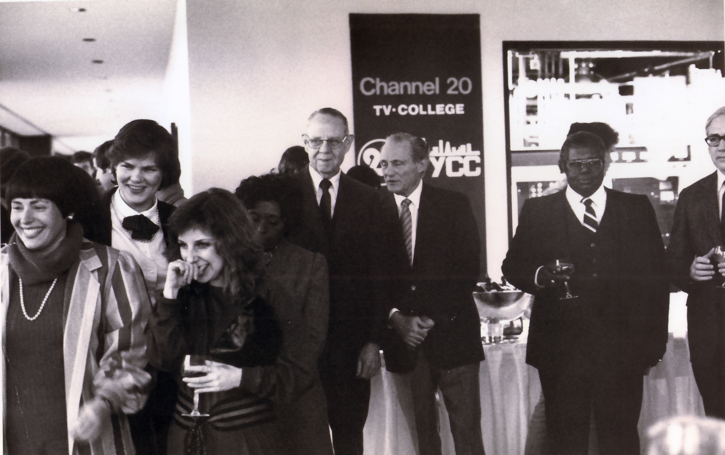 The Premiere Broadcast. L-R: (front row) Elynne Chaplik-Aleskow; Shelly Pazzol, director of Public Relations (second row)  Ginny McGann, director of station operations; unidentifield board member; (back row) unidentified board member, Chancellor Oscar Shabat, two unidentifield board members